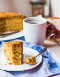 Eating a teaspoon of honey cake with sour cream Royalty Free Stock Photos