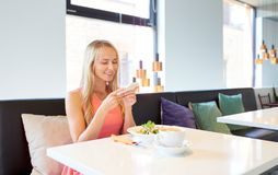 Happy woman with smartphone eating at restaurant Royalty Free Stock Images