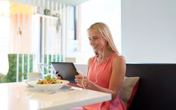 Happy young woman with tablet pc at restaurant Stock Photo