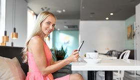 Happy young woman with tablet pc at restaurant stock photos