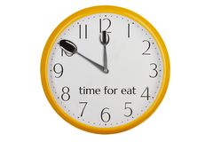 Eating time concept. Yellow kitchen wall clock reminding about meal time Stock Photography
