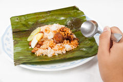 Eating the traditional banana leaf wrapped nasi lemak. Stock Photo