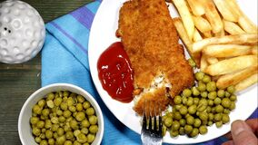 Eating Traditional Fish And Chips With Peas And Tomato Sauce stock footage