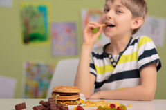 Eating unhealthy snacks for lunch. School child eating unhealthy snacks for lunch royalty free stock images