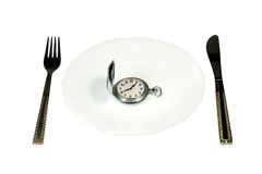 "Eating up time. Dining table and antique pocket watch on a white plate (""eating up time"" concept Stock Photography"