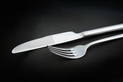 Eating utensils/fork and knife on black background Royalty Free Stock Image