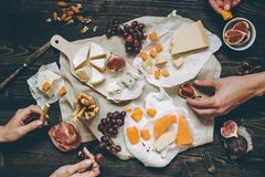 Eating various types of cheese with fruits and snacks on the wooden dark table. royalty free stock images