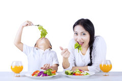 Eating vegetables with mother on white Royalty Free Stock Photos