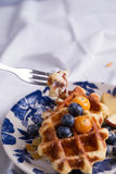 Eating waffle. Closeup of a fork cutting a piece of blueberry waffle decorated with fresh blueberry in a nice dish Stock Images