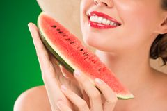 Eating watermelon. Close-up image of unrecognizable woman with red lips eating watermelon Stock Photography