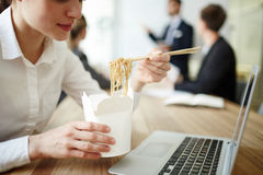 Eating at work. Businesswoman eating takeout noodles from box by workplace in front of laptop Royalty Free Stock Photos
