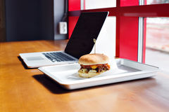 Eating at work place - fast food. burger near laptop. lunch break while you work or sharing online Royalty Free Stock Images