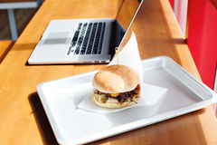 Eating at work place - fast food. burger near laptop. lunch break while you work or sharing online Stock Photography