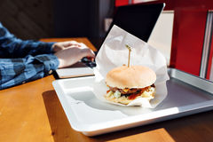 Eating at work place - fast food. burger near laptop. lunch break while you work or sharing online. typing on the Stock Photography