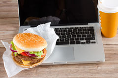 Eating at work place fast food near laptop. On wooden table Stock Image