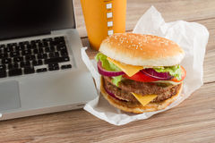 Eating at work place near laptop. Eating at work place  fast food near laptop Royalty Free Stock Images