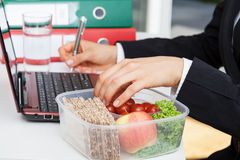 Eating and working Stock Images