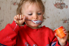 Eating yogurt. Little baby eating yogurt stock photo