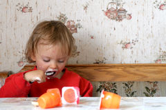 Eating yogurt. Little baby eating yogurt Stock Image