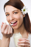 Eating yogurt. Young beautiful woman eating yogurt close up Royalty Free Stock Image