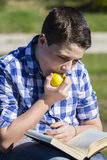 Eating.Young man reading a book in outdoor with yellow apple. Portrait. Young boy reading a book in wooden stairs, summer scene Stock Images