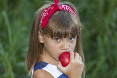 She eats an apple and looks at the camera royalty free stock images