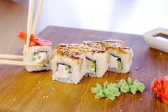Eats rolls with fish and sesame seed on top served in wooden board with wasabi, ginger and soy sause. Wood sticks close. Up royalty free stock images