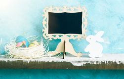Eatser mock up with chalkboard, painted eggs in nest and white wooden bunny on shelf against blue wall. Scandinavian style. Text space Royalty Free Stock Photo