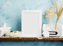 Eatser verspotten oben mit photoframe, gemalten Eiern im Nest und weißem hölzernem Häschen auf Regal gegen blaue Wand Skandinavis Stockbild