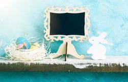 Eatser verspotten oben mit Tafel, gemalten Eiern im Nest und weißem hölzernem Häschen auf Regal gegen blaue Wand Skandinavische A Lizenzfreies Stockfoto