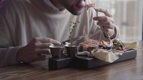 eatting令人敬畏的可口盘用烤肉和菜的人的关闭坐在豪华餐馆 影视素材