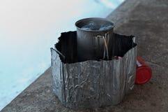 Eau bouillante dans la tasse titanique sur la cuisinière à gaz blanche photographie stock libre de droits