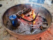 Eau bouillante de vieille cafetière bleue sur le feu de camp Images libres de droits