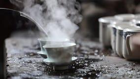 Eau chaude de versement dans la tasse de thé de porcelaine banque de vidéos