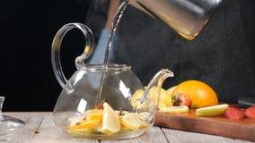 Eau chaude de versement dans la théière avec le fruit coupé en tranches Théière en verre avec l'orange et le citron à l'intérieur banque de vidéos
