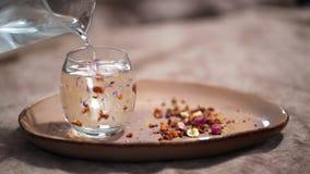 Eau chaude de versement dans le verre avec le thé coloré et sec clips vidéos