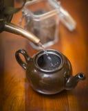 Eau chaude de versement dans une bouilloire de thé Images stock