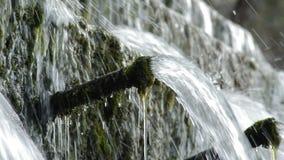 Eau de rivière fonctionnant dans la naissance d'un riverPipe dans la roche expulsant l'eau de montagne dans la naissance d'une ri banque de vidéos