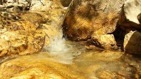 Eau de rivière de montagne circulant sur des roches banque de vidéos