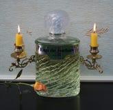 Eau de Rochas, Duft für Damen, große Parfümflasche vor Kandelaber mit den glänzenden Kerzen verziert mit einer Rose stockbilder
