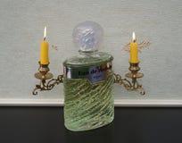 Eau de Rochas, Duft für Damen, große Parfümflasche vor Kandelabern eines Klaviers mit glänzenden Kerzen stockfotos