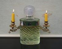 Eau de Rochas, Duft für Damen, große Parfümflasche vor Kandelabern eines Klaviers mit glänzenden Kerzen lizenzfreies stockbild