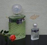 Eau De Rochas, woń dla dam, wielka pachnidło butelka obok handlowej pachnidło butelki przed atłasowym wallcovering zdjęcie royalty free