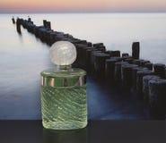 Eau De Rochas, woń dla dam, wielka pachnidło butelka przed obrazkiem groyne w morzu zdjęcie royalty free