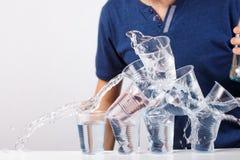 Eau douce de débordement dans un verre en plastique Image stock