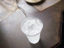 Eau douce de versement au verre de glace Photographie stock