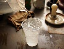 Eau douce de versement au verre de glace Photos stock
