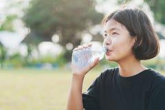 eau douce potable asiatique de petite fille de bouteille en plastique avec Images stock