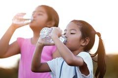 Eau douce potable de fille asiatique mignonne de petit enfant de bouteille photo libre de droits