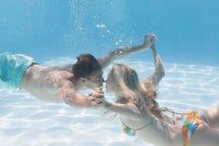 Eau du fond de baiser de couples mignons dans la piscine Images libres de droits